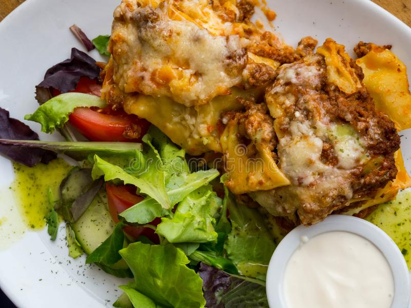 Tasty serving of traditional Italian lasagne with spicy tomato based ground beef and melted mozzarella cheese between layers of stock photography