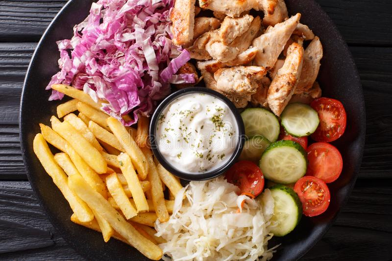 Tasty shawarma bowl with chicken, french fries, vegetables and sauce close-up. Horizontal top view stock image