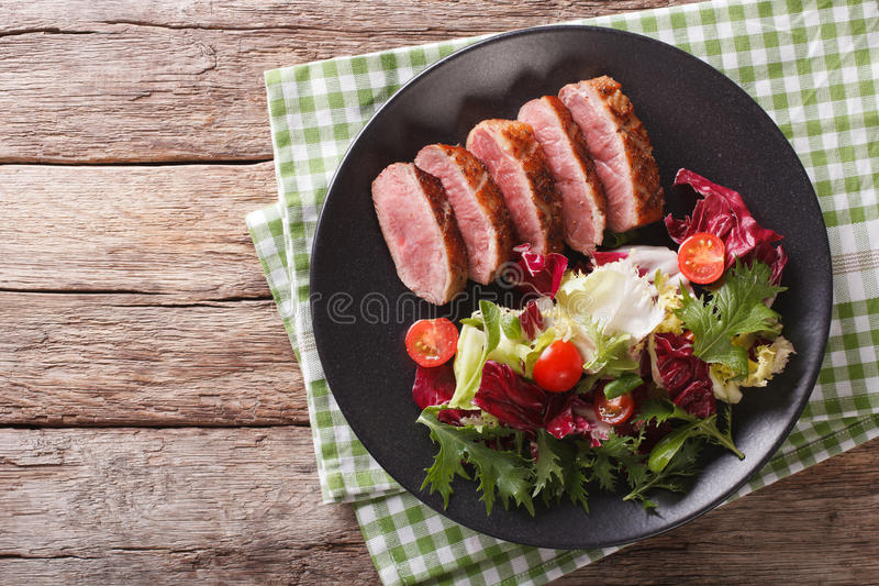 Tasty sliced roast duck breast with fresh vegetable salad close-up. Horizontal top view royalty free stock images