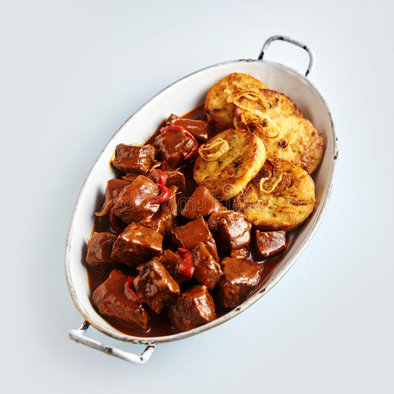 Tasty spicy beef goulash with dumplings stock image