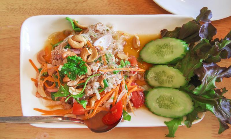 Tasty spicy thai glass noodle salad with pork top view on white plate royalty free stock photos