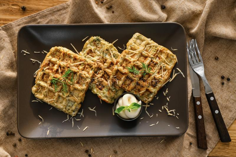 Tasty squash waffles with sauce on plate royalty free stock image