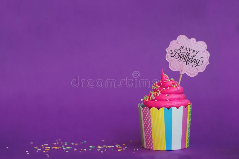 Tasty strawberry cupcake with sprinkles and Happy Birthday banner on violet background. Party background stock image