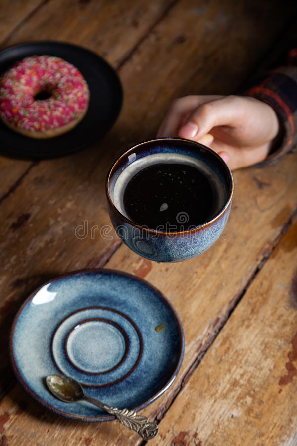 Tasty strawberry sprinkled donut, vintage tea spoon, black americano coffee in blue cup in male hand. Concept breakfast in coffee stock images
