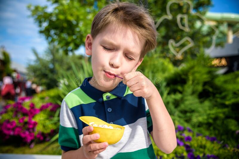 Tasty summer obsession concept. Happy young kid handsome hipster boy wearing colorful polo t-shirt, eating mini melts ice cream in royalty free stock photo