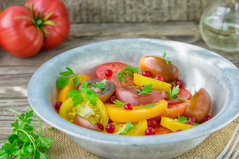 Tasty summer salad of sliced fresh colorful tomatoes, chopped red onion with white currant berries, olive oil, and parsley. Healt. Hy meal stock images