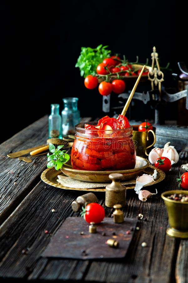 Tasty sun dried tomatoes with garlic, pepper, basil, olive oil in glass jar stands on brass plates on rustic wooden table. With weights and old scales with royalty free stock photo