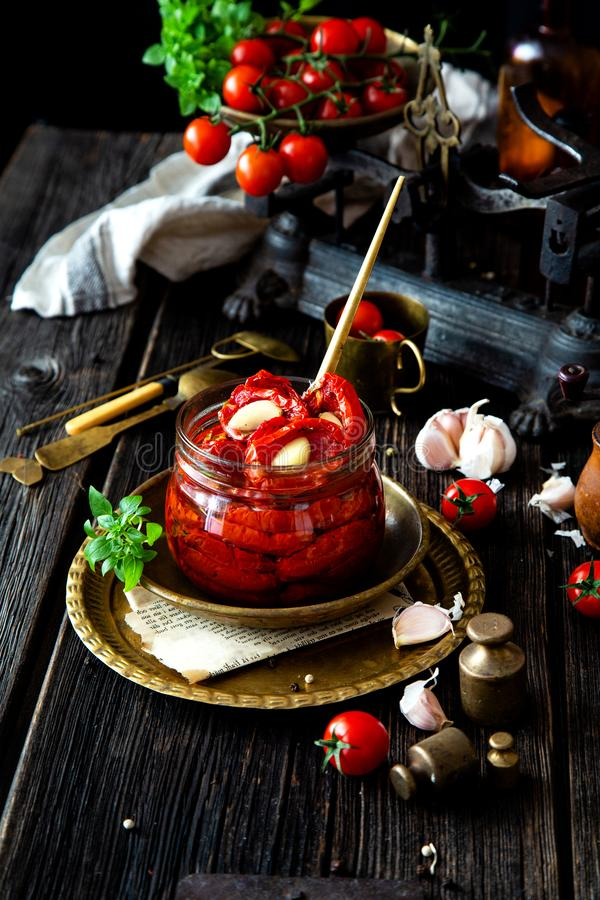 Tasty sun dried tomatoes with garlic, pepper, basil, olive oil in glass jar stands on brass plates on rustic wooden table. With weights and old scales with stock images