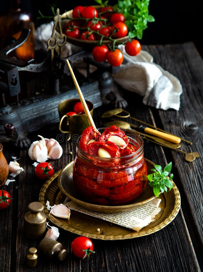 Tasty sun dried tomatoes with garlic, pepper, basil, olive oil in glass jar stands on brass plates on rustic wooden table. With weights and old scales with royalty free stock photography