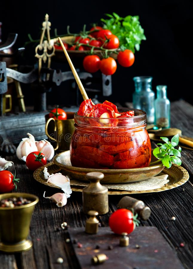 Tasty sun dried tomatoes with garlic, pepper, basil, olive oil in glass jar stands on brass plates on rustic wooden table. With weights and old scales with stock photos