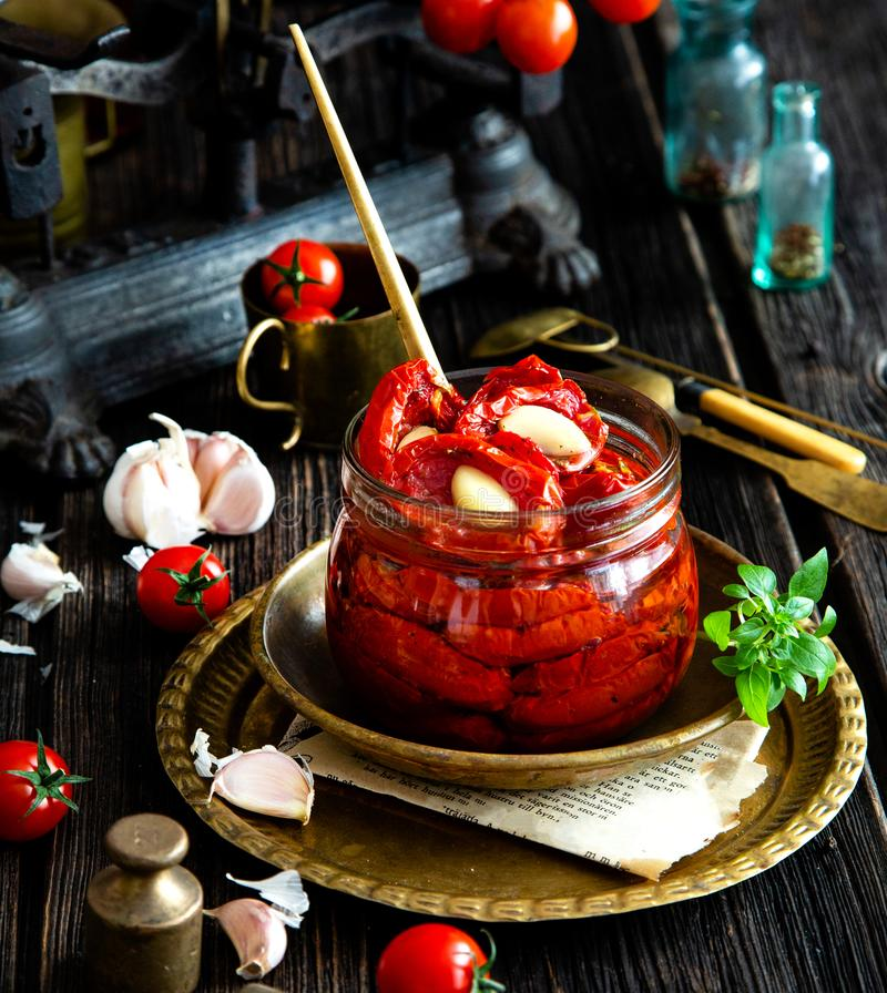 Tasty sun dried tomatoes with garlic, pepper, basil, olive oil in glass jar stands on brass plates on rustic wooden table. With weights and old scales with stock photo