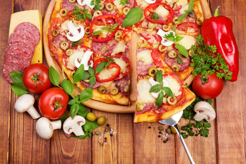 Tasty Supreme Pizza. Supreme Pizza with tasty slice on wooden table background royalty free stock photography