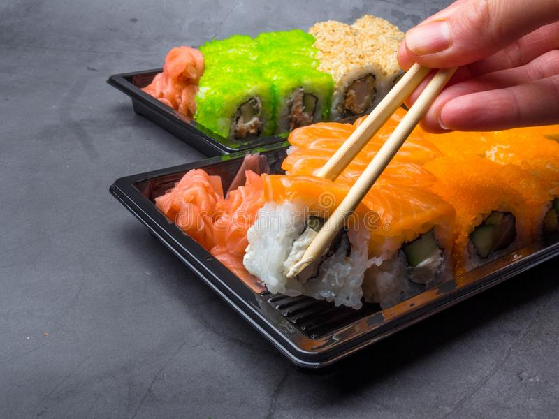 Tasty sushi bar, Eating Sushi with chopsticks. California Sushi roll set with salmon, vegetables, fish, caviar closeup. Japan royalty free stock photos