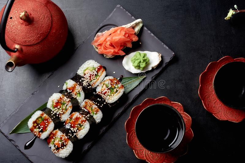 Tasty sushi roll on black stone plate and chinese sause with ginger and wassabi. Chinese cousine royalty free stock images