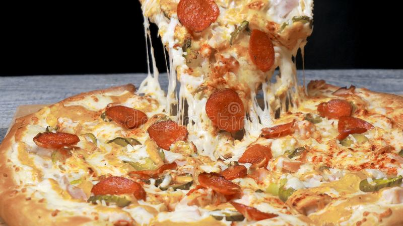 Tasty take slice of pizza with cheese. Frame. Appetizing separate piece of round pizza stretching melted cheese. Juicy stock image