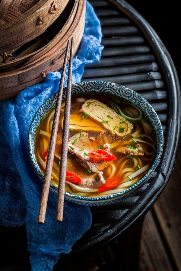 Tasty Thai broth in black bowl with chopsticks stock image