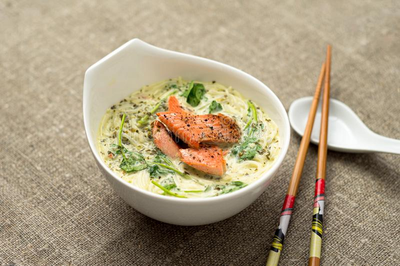 Tasty Thai coconut soup with noodles. One of the most popular Thai food, tom kha is a spicy and sour soup with coconut milk. Vermicelli noodles and salmon are royalty free stock photos