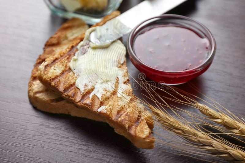 Tasty toast with butter and sweet jam on table stock images