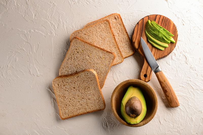 Tasty toasted bread with cut avocado on white table royalty free stock image