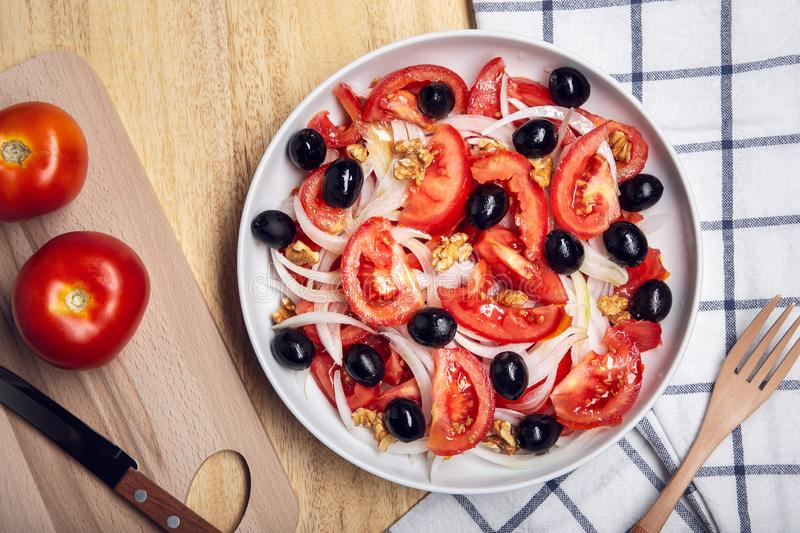 Tasty tomato salad with onion and black olives on plate. Mediterranean food royalty free stock photography