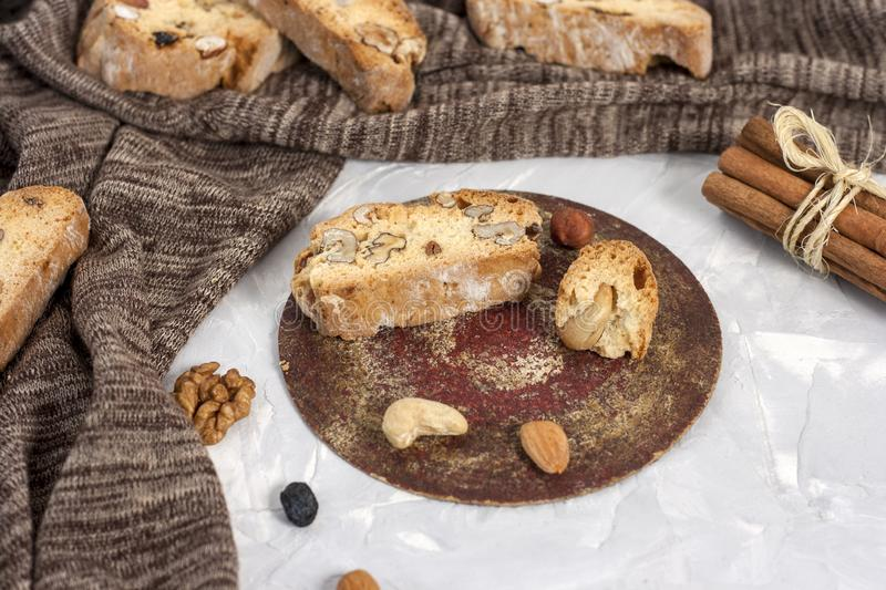 Tasty traditional Italian homemade biscotti or cantuccini cookies with hazelnuts, almonds and walnuts on a light gray background.  stock photos