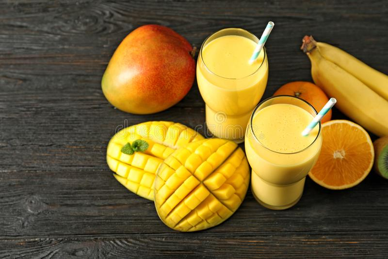 Tasty tropical drink with mango and fresh fruits. On wooden table stock photo