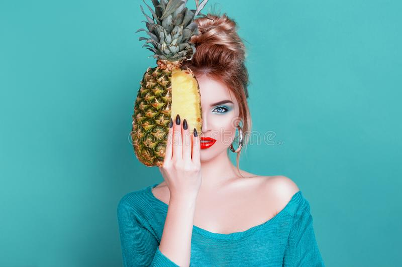 Tasty tropical fruits! Attractive sexual woman with beautiful makeup holding fresh juicy pineapple and looking at cam on. Blue background. Summer Fashion royalty free stock image