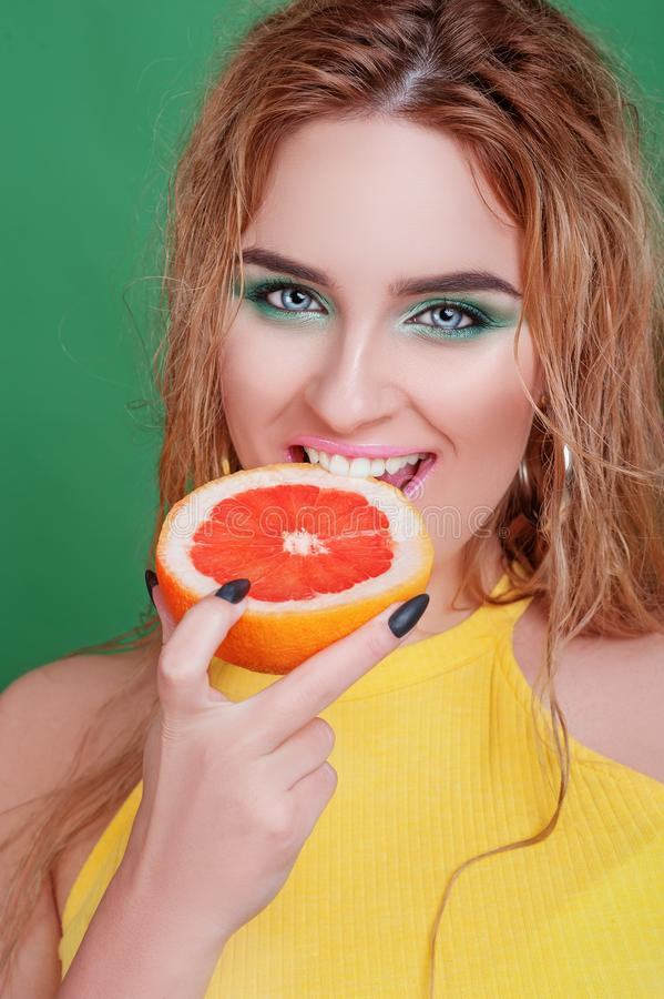 Tasty tropical fruits! Attractive sexual woman with beautiful makeup and wet hair eating fresh juicy grapefruit or orange smiling stock photo