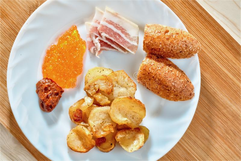 Tasty unhealthy food. Greasy fried. Potatoes, bacon, red caviar, spicy sauce and white bread on a white plate. Snacking stock photos