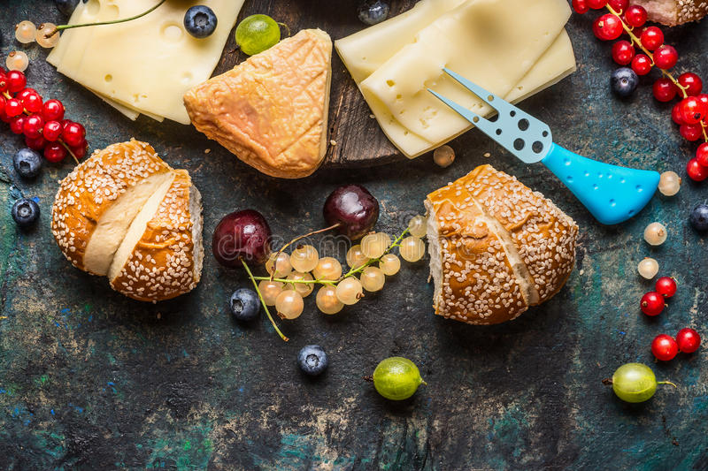 Tasty various cheese with buns and berries for breakfast stock images