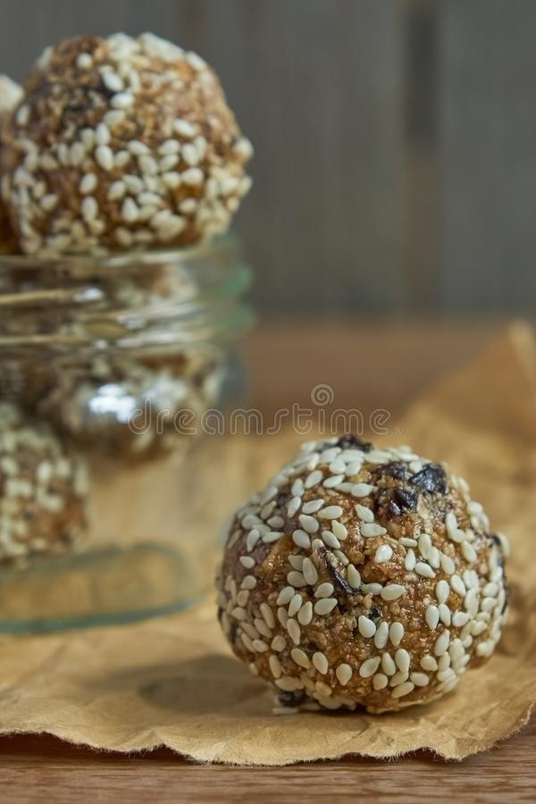 Tasty vegan raw protein truffles or energy balls with prunes, seeds and nuts in a jar on wooden background royalty free stock photos