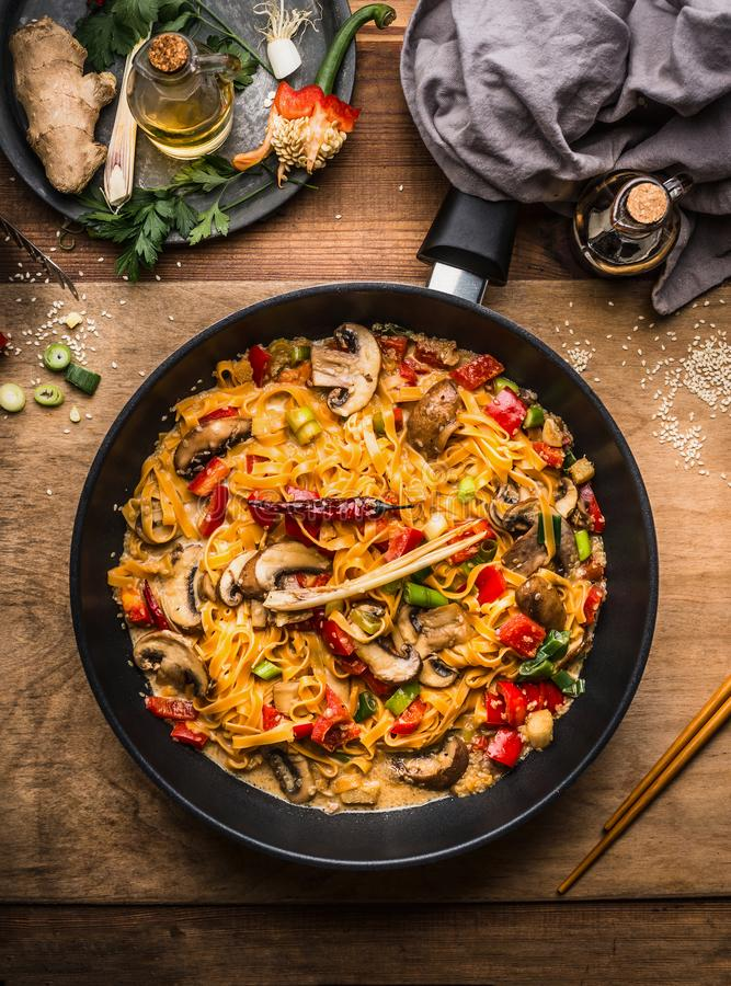Tasty vegetarian fried noodles pan with vegetables and creamy pasta sauce on wooden background royalty free stock photography