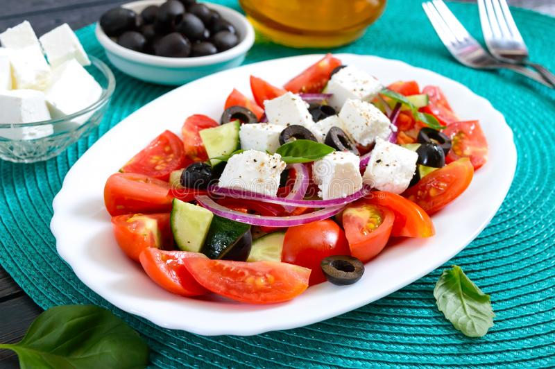 Tasty  vitamin salad with fresh vegetables, feta, black olives, basil sauce on a white plate on a wooden background royalty free stock photos