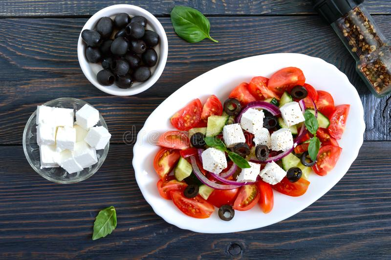 Tasty  vitamin salad with fresh vegetables, feta, black olives, basil sauce on a white plate on a wooden background. Top view royalty free stock image