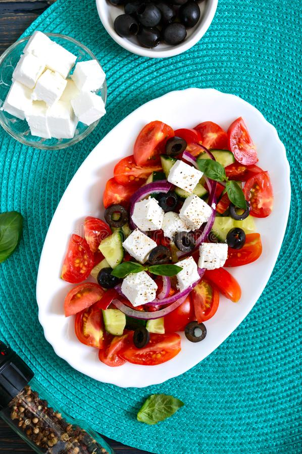 Tasty  vitamin salad with fresh vegetables, feta, black olives, basil sauce on a white plate on a wooden background. Top view stock photos