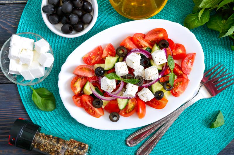 Tasty  vitamin salad with fresh vegetables, feta, black olives, basil sauce on a white plate on a wooden background. Top view stock image