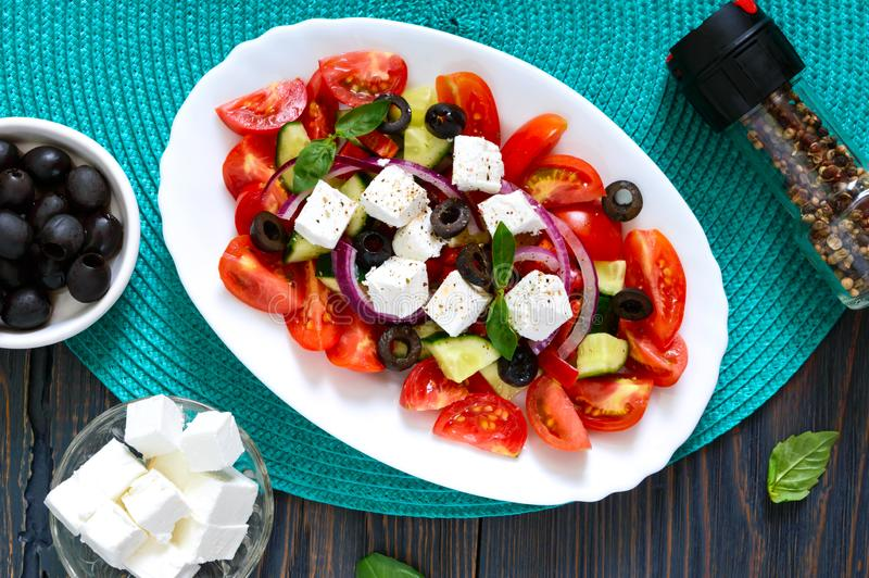 Tasty  vitamin salad with fresh vegetables, feta, black olives, basil sauce on a white plate on a wooden background. Top view stock images
