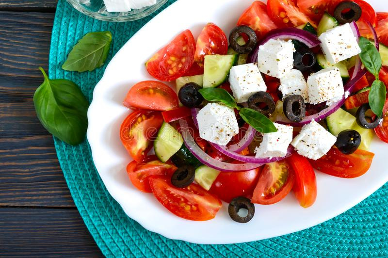 Tasty  vitamin salad with fresh vegetables, feta, black olives, basil sauce on a white plate on a wooden background. Top view. royalty free stock photo
