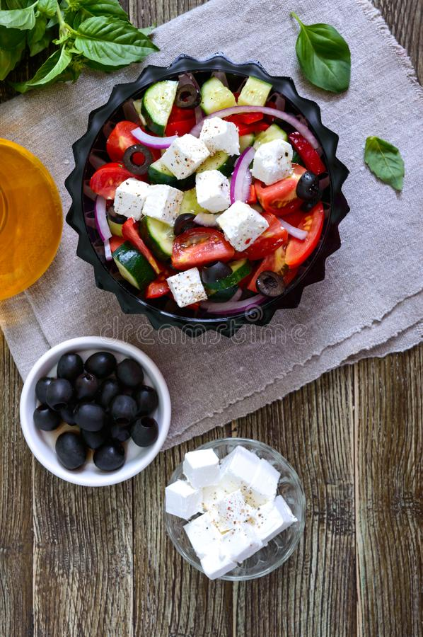 Tasty  vitamin salad with fresh vegetables, goat cheese, black olives, basil sauce on a white plate on a wooden background. Top stock photography
