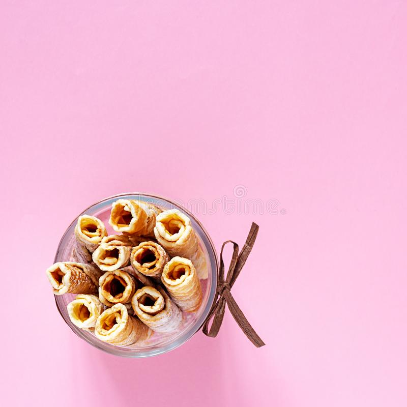 Tasty wafer rolls with icing sugar in a glass bowl. Homemade baking. Tasty wafer rolls with icing sugar in a glass bowl with decorative design on a pink royalty free stock images