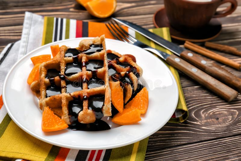 Tasty waffles with chocolate and orange on plate stock photos