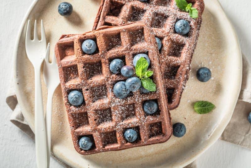 Tasty waffles made of dark chocolate on white table stock photo