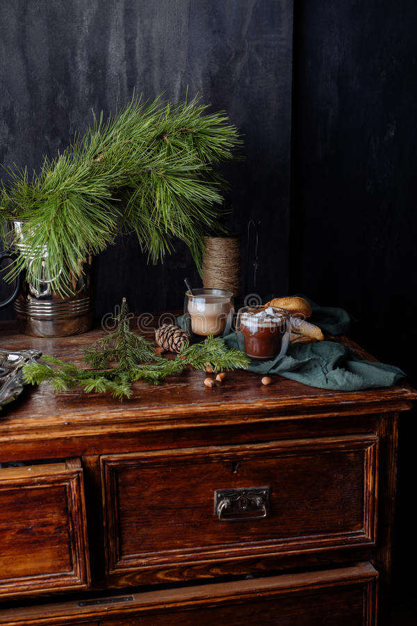 Tasty warm cocoa on an ancient dresser. It is decorated by fir-tree branches and a green scarf stock image