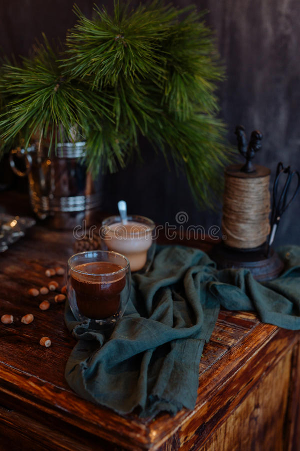 Tasty warm cocoa on an ancient dresser. It is decorated by fir-tree branches and a green scarf royalty free stock image