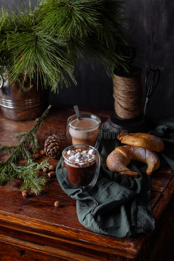 Tasty warm cocoa on an ancient dresser. It is decorated by fir-tree branches and a green scarf royalty free stock images