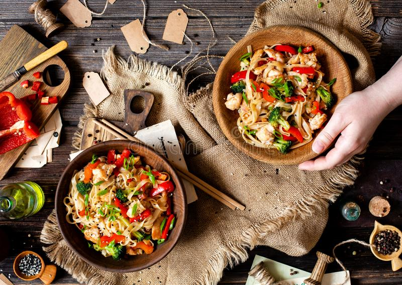 Homemade tasty wok noodles with fried chicken fillet, broccoli, red ball pepper, green onion, sesame stock photo