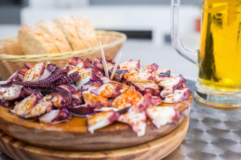 Tasty Wooden plate of galician style cooked octopus with paprika and olive oil. Pulpo a la gallega.  royalty free stock photography