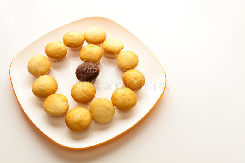 Tasty yellow muffins and chocolate muffin in center. Tasty muffins in the plate on the table near to window with natural sun light stock photos