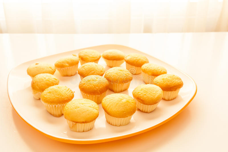 Tasty yellow muffins in a white plate. Tasty muffins in the plate on the table near to window with natural sun light stock photos