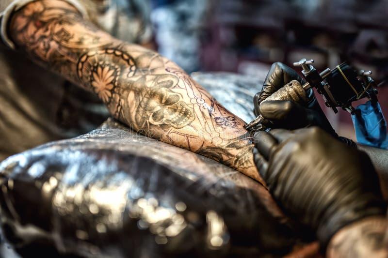Tatúe el dibujo del artista en el brazo y en la piel del cliente imagen de archivo